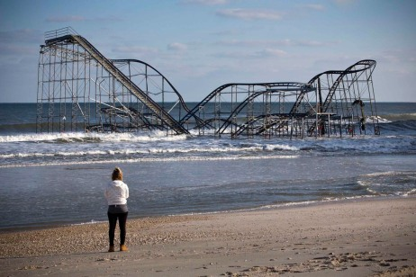 A woman looks at a roller coaster sitting in the ocean, when the boardwalk it was built upon collapsed during Hurricane Sandy, in Seaside Heights, New Jersey